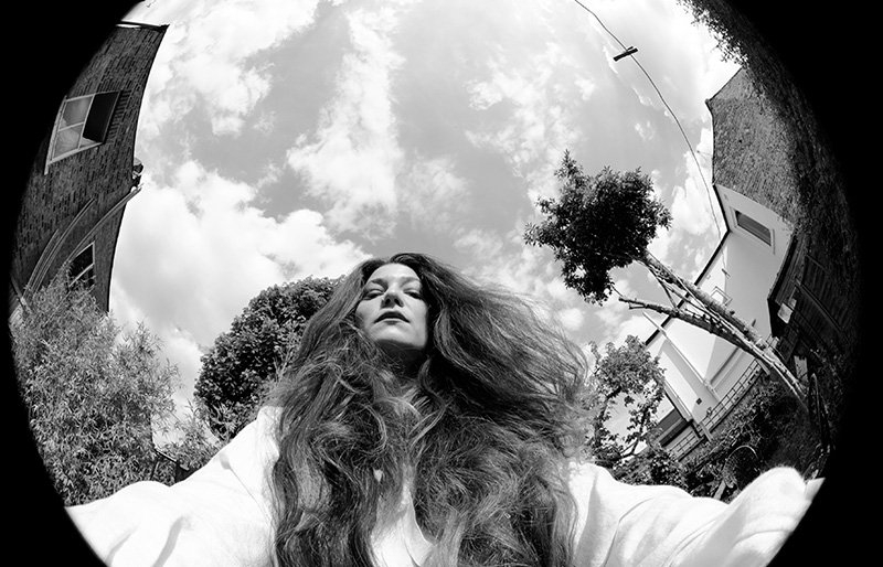 A black-and-white self-portrait of a woman taken with a fisheye lens
